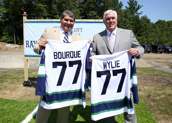 Boston Bruins legendary defenseman Ray Bourque poses with Endicott College President Richard Wylie holding Endicott College hockey jerseys at a groundbreaking ceremony for the new ice hockey rink at Endicott College, which will be named the Raymond J. Bourque Arena and is set to be completed in fall 2015. DAVID LE/Staff photo. 7/29/14.