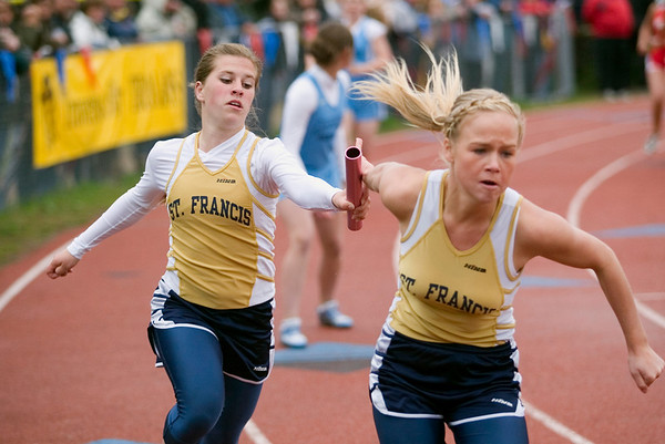 Record-Eagle/Jan-Michael Stump<br /> Traverse City St. Francis' Danielle Bott hands off to Hannah Johnson in the 800 meter relay.