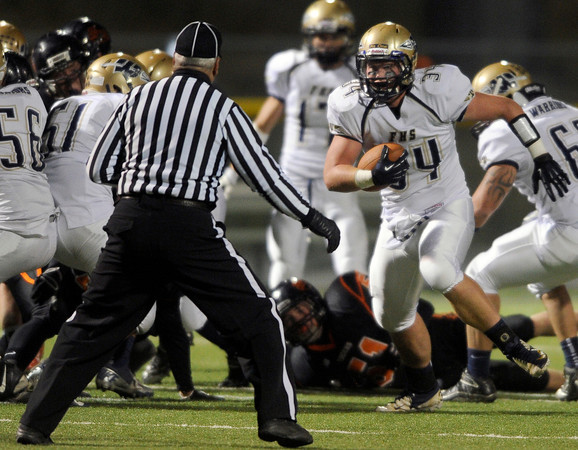 "Frederick High School's Ryan Miller, No. 34, runs the ball straight at the referee during a football game on Friday, Oct. 5, against Erie High School at Erie High School. For more photos of the game go to  <a href=""http://www.dailycamera.com"">http://www.dailycamera.com</a><br /> Jeremy Papasso/ Camera"