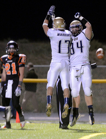 "Erie High School's Christian Mickey, left, watches as Jacob Sleeth, No. 17, and Ryan Miller, No. 34, celebrate a touchdown during a football game on Friday, Oct. 5, at Erie High School. For more photos of the game go to  <a href=""http://www.dailycamera.com"">http://www.dailycamera.com</a><br /> Jeremy Papasso/ Camera"