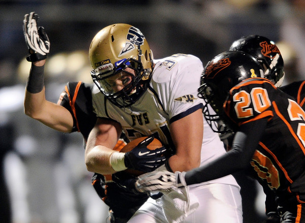 "Frederick High School's Ryan Miller holds the ball while rushing into Ryan True, No. 20, and others during a football game on Friday, Oct. 5, against Erie High School at Erie High School. For more photos of the game go to  <a href=""http://www.dailycamera.com"">http://www.dailycamera.com</a><br /> Jeremy Papasso/ Camera"