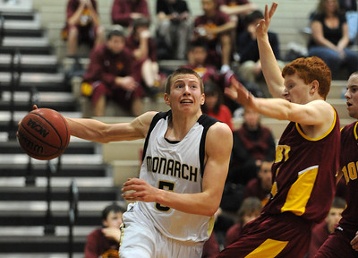 Nate McGinley of Monarch, drives around Michael Hoppal of Rocky Mountain on Friday.  For more photos of Monarch, go to www.dailycamera.com. Cliff Grassmick / January 15, 2010