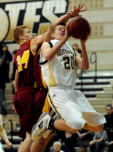 Isaac Spence of Monarch goes up and under Ethan Karp of Rocky Mountain on Friday night.  For more photos of Monarch, go to www.dailycamera.com. Cliff Grassmick / January 15, 2010