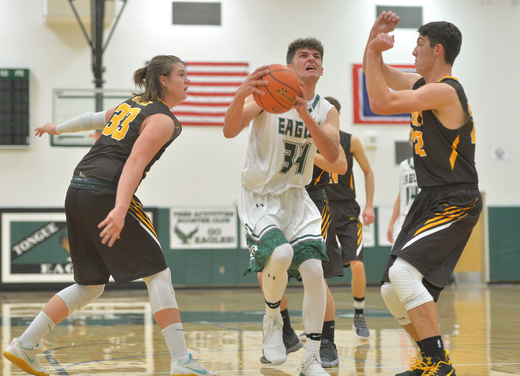 Justin Sheely | The Sheridan Press<br /> Tongue River's Jaren Fritz goes for a layup against Rocky Mountain's Colby Davison, left, and Taylor Winland at Tongue River High School Friday, December 8, 2017. The Eagles lost to Rocky Mountain 85-40.