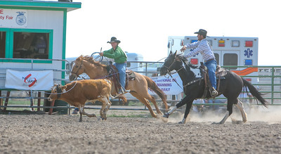 Day one of the Panhandle High School Rodeo, at Scotts Bluff County Fairgrounds in Mitchell, NE. In the Team Roping Austin Willey of Bayard and Brock Henry (in Green) of Rushville.