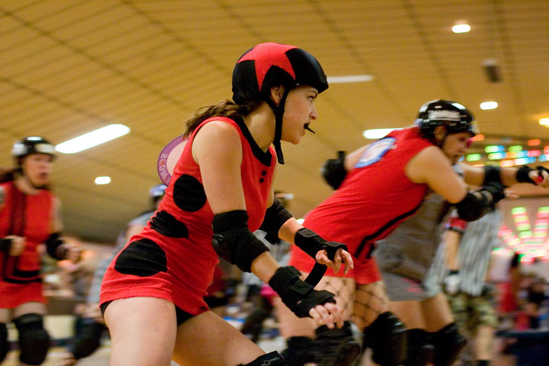 The Mobtown Mods' jammer, Dissin' Kari, (with mouth-guard, in case you were wondering) passes on the outside with protection from her team mates in their bout with the Junkyard Dolls.