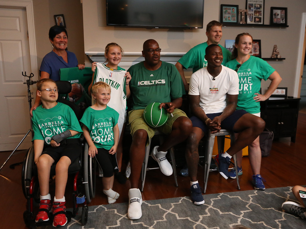 . Plotkin family in Groton, Erik and wife Erin Plotkin, right, son Tyler, 14, left, who had brain surgery as an infant, daughter Alisa, 11, and son Gavin, 5, gets a backyard basketball court, with a visit by Boston Celtics\' Terry Rozier, seated left, and retired legend Cedric Maxwell, center. At left rear is Arbella Insurance director of corporate communications Maryanne Hailer. (SUN/Julia Malakie)