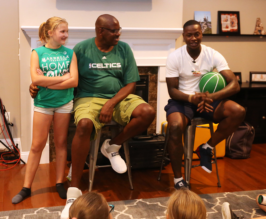 . Plotkin family in Groton gets a backyard basketball court, with a visit by Boston Celtics\' Terry Rozier, and retired legend Cedric Maxwell. Alisa Plotkin, 11, and Cedric Maxwell listen to Terry Rozier. (SUN/Julia Malakie)
