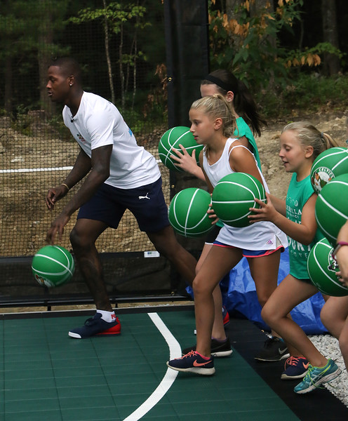 Plotkin family in Groton gets a backyard basketball court, with a visit by Boston Celtics' Terry Rozier, and retired legend Cedric Maxwell. Rozier does a dribbling drill with the kids. (SUN/Julia Malakie)