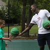 Plotkin family in Groton gets a backyard basketball court, with a visit by Boston Celtics' Terry Rozier, and retired legend Cedric Maxwell. Terry Rozier hands a ball back to John Ryan, 7, of Concord, who'd volunteered to try free throws. (SUN/Julia Malakie)