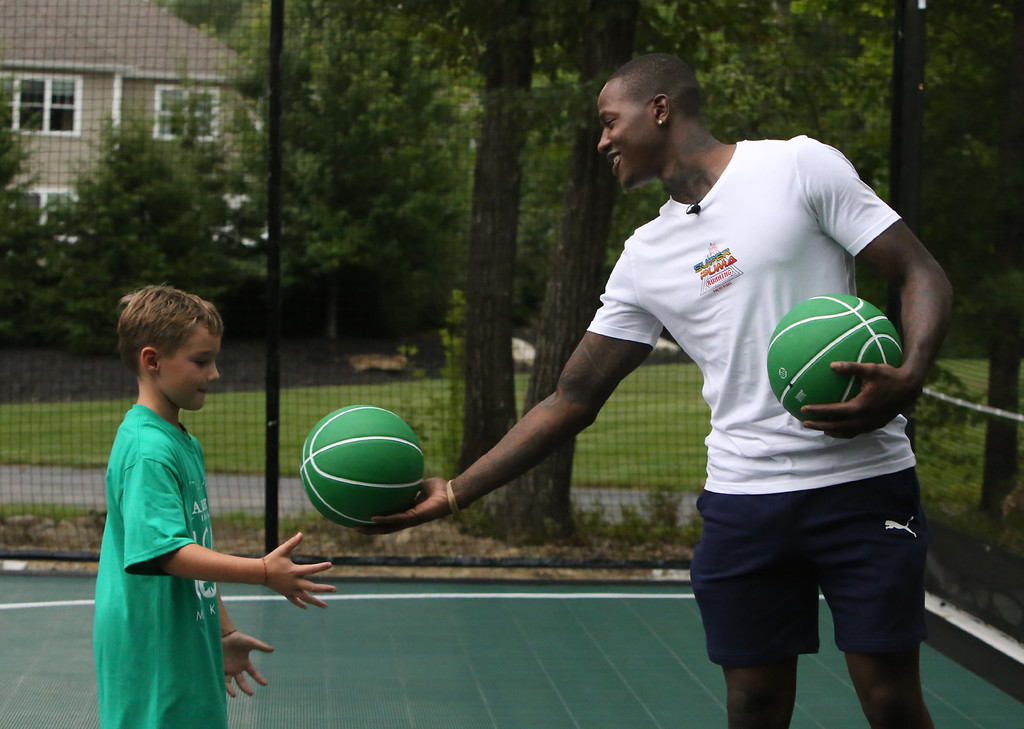 . Plotkin family in Groton gets a backyard basketball court, with a visit by Boston Celtics\' Terry Rozier, and retired legend Cedric Maxwell. Terry Rozier hands a ball back to John Ryan, 7, of Concord, who\'d volunteered to try free throws. (SUN/Julia Malakie)