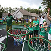 Plotkin family in Groton gets a backyard basketball court, with a visit by Boston Celtics' Terry Rozier, right rear, and retired legend Cedric Maxwell, left, Family members shooting for the basket are Tyler, 14, his sister Alisa, 11, and parents Erik and Heather Plotkin. (SUN/Julia Malakie)