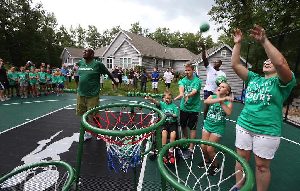 . Plotkin family in Groton gets a backyard basketball court, with a visit by Boston Celtics\' Terry Rozier, right rear, and retired legend Cedric Maxwell, left, Family members shooting for the basket are Tyler, 14, his sister Alisa, 11, and parents Erik and Heather Plotkin. (SUN/Julia Malakie)