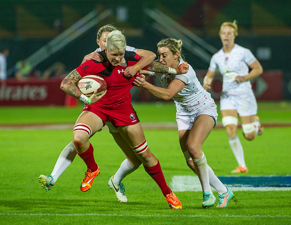 Canada's Jennifer Kish attempts to hand off the English defence in the Pool C match during the first day of the IRB Women's Sevens World Series rugby tournament at the Emirates Airline Dubai Rugby Sevens in Dubai, UAE, Thursday, Dec. 4th, 2014. Photo by: Stephen Hindley/Sportdxb/Photosport