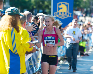 062412, Boston, MA - Runner Kim Smith of Providence celebrates with the crowd after earning a first place finish in the women's division of Second Annual Boston Athletic Assicoation 10K with a final time of 31:36. Herald photo by Ryan Hutton