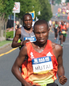 062412, Boston, MA - Runner Philip Langet tries to keep pace with Geoffrey Mutai of Kenya as the latter breaks away from the pack during the final few kilometers of the Second Annual Boston Athletic Assicoation 10K. Herald photo by Ryan Hutton