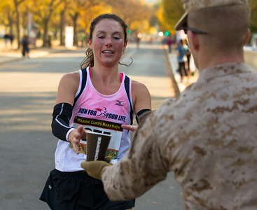 Alice Rodgers of Charlotte NC grabs a cup of powerade from Marine Second Lieutenant Robert Grundmeier on the National Mall during the running of the Marine Corps Marathon on Oct. 31, 2010.