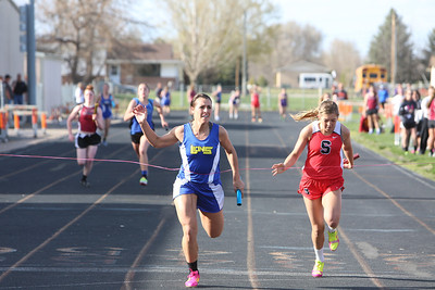 Morrill's Shalyn Lackey  crosses the finish line in the girls 4x100 relay. Sidney's Gabbie Addleman to the right.