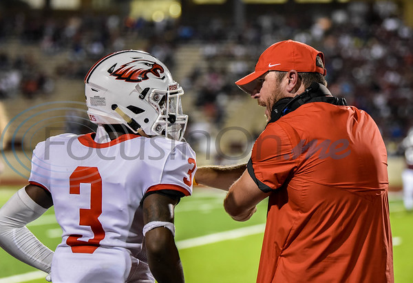 First year Rusk Eagles head coach Thomas Sitton goes over a play on the sidelines with senior Isiah Ward (3) during a game against the Palestine Wildcats on Friday. The Wildcats went on to win the game 23-13.