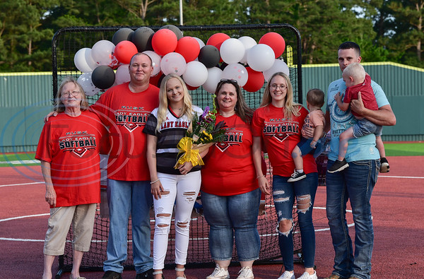 Rusk senior Alanna Goldsberry (center) smiles while holding flowers with her family during a surprise Senior Softball Night party on Wednesday, May 13. The seniors took the field for the last time to be honored as their season was cut short due to the coronavirus.