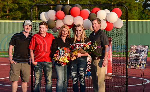 Rusk senior Grace Young (center) smiles while holding flowers with her family during a surprise Senior Softball Night party on Wednesday, May 13. The seniors took the field for the last time to be honored as their season was cut short due to the coronavirus.