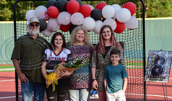 Lanie Ford (second from left) smiles while holding flowers with her family during a surprise Senior Softball Night party on Wednesday, May 13. The seniors took the field for the last time to be honored as their season was cut short due to the coronavirus.