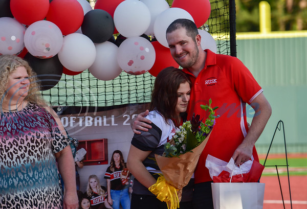Rusk senior softball player Lanie Ford hugs new Head Coach Michael Williams while her mother Ruthann Ford looks on with a smile. The seniors were honored on the field during a revised Senior Softball Night due to the coronavirus on Wednesday, May 13.