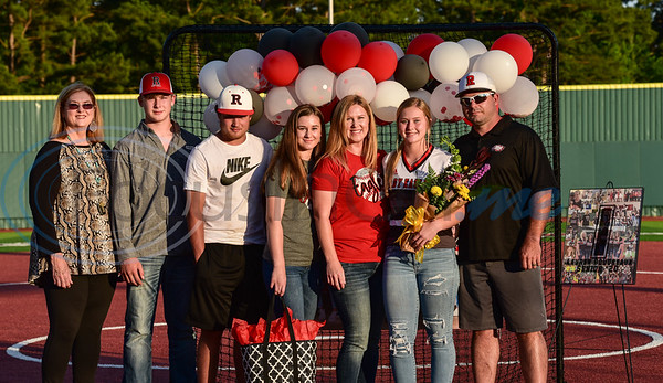 Lauren Boudreaux (second from right) smiles while holding flowers with her family during a surprise Senior Softball Night party on Wednesday, May 13. The seniors took the field for the last time to be honored as their season was cut short due to the coronavirus.