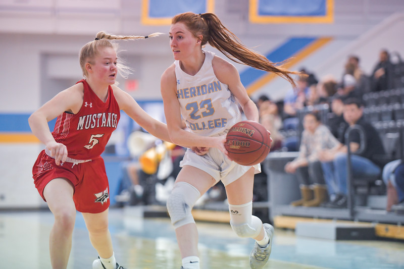 Ashleigh Snoozy | The Sheridan Press<br>Sheridan's Darcy Walker (23) moves past the Western Wyoming Community College defender Tori Ross (5) at Sheridan College Saturday, Feb. 1, 2020.