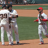 Local boy Jimmy Rollins passes by Pablo and first base coach Roberto Kelly as he makes his way to the dugout.