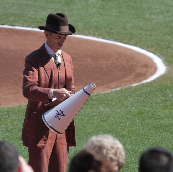 Man with the bullhorn announces current events of the time (100 years ago) between innings.