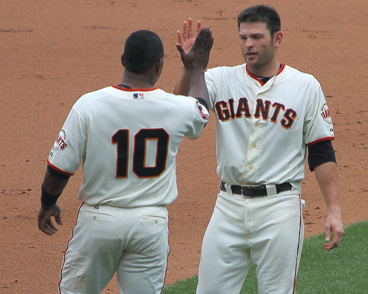 Miguel Tejada and Freddy Sanchez high-five after teaming to score a run.
