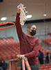 South Grand Prairie Head Coach Brian Raven cuts the net after a decisive win by his girls basketball team over Plano East in the Regional Finals Playoff.