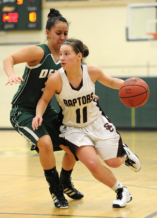 20120224_BKOI_71.jpg Silver Creek High School's Ana Gurau (No. 11) drives around Delta High School's Sadie Carrillo (No. 21) during the third quarter Friday, Feb. 24, 2012 at D'Evelyn High School. The Raptors were defeated by the Panthers, 50-47.<br /> (Matthew Jonas/Times-Call)