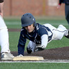 Lawrence's Edison Urena dives back to first base on a pickoff attempt.