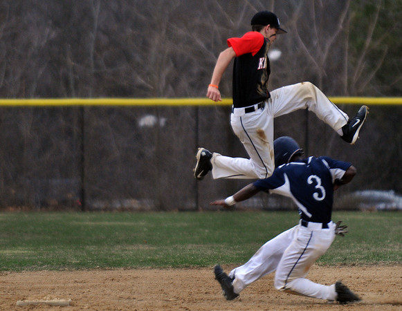 North Andover's short stop, captain Matthew Varoutsos leaps over Lawrence's Elvis Peralta after catching the high throw and managed to tag him out. 4/11/2014.