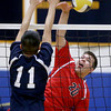Central Catholic player Nick Cambio spikes the ball past the defensive efforts of Daniel Lee.