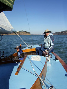 "Ron's lady friend Joan Wheeler handling tiller and Silas Lambros - Sailing on San Francisco Bay on Ron Young's classic wooden boat ""Youngster"""