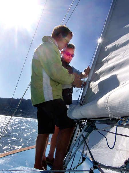 """Left, Marc Lambros and Right, Ron Young checking lines and sails - Sailing on San Francisco Bay on Ron Young's classic wooden boat """"Youngster"""""""
