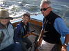 """Joan Wheeler, Ron's lady friend, left; Silas, Marc Lambros' son, center, and Ron Young, right - Sailing on San Francisco Bay on Ron Young's classic wooden boat """"Youngster"""""""
