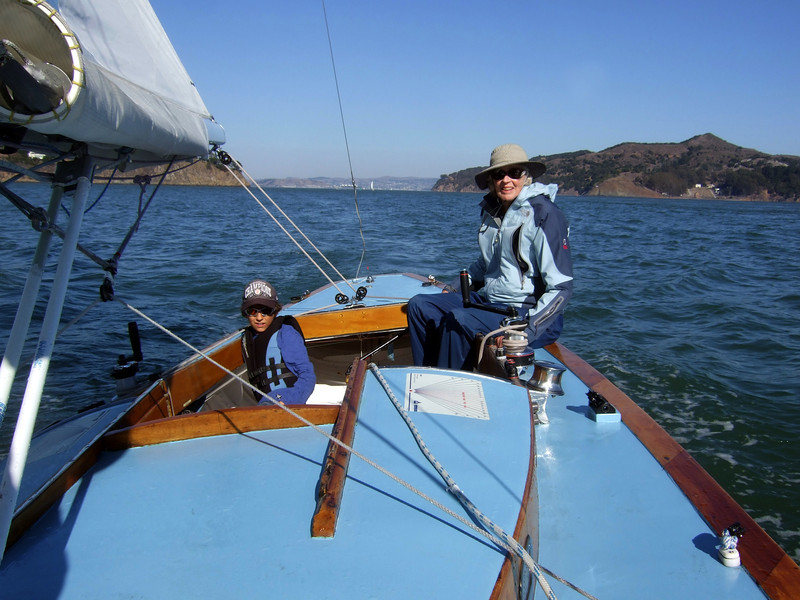 """Ron's lady friend Joan Wheeler handling tiller and Silas Lambros - Sailing on San Francisco Bay on Ron Young's classic wooden boat """"Youngster"""""""