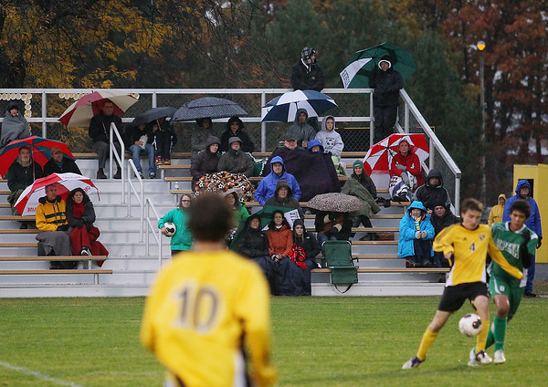 Record-Eagle/Keith King<br /> Spectators try to stay dry as it rains during the game between Traverse City Central and Alpena Thursday, October 18, 2012 at the Coast Guard Field in Traverse City.