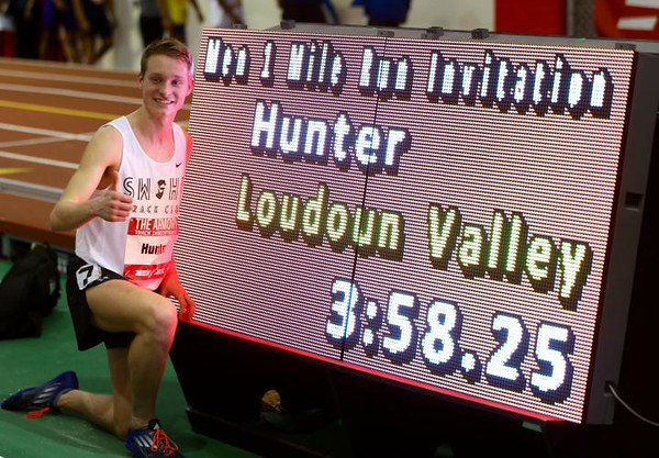 Drew Hunter poses next to the clock at the Armory Invitational after breaking a four-minute mile. PROVIDED PHOTO