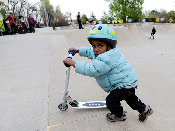 Zuru Sjong, 3, pushes his scooter out of traffic at Scott Carpenter Park on Thursday.<br /> Cliff Grassmick / May 13, 2010