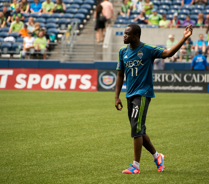 Leaving the pitch to ready for the first half, Zakuani raises a hand for the fans.