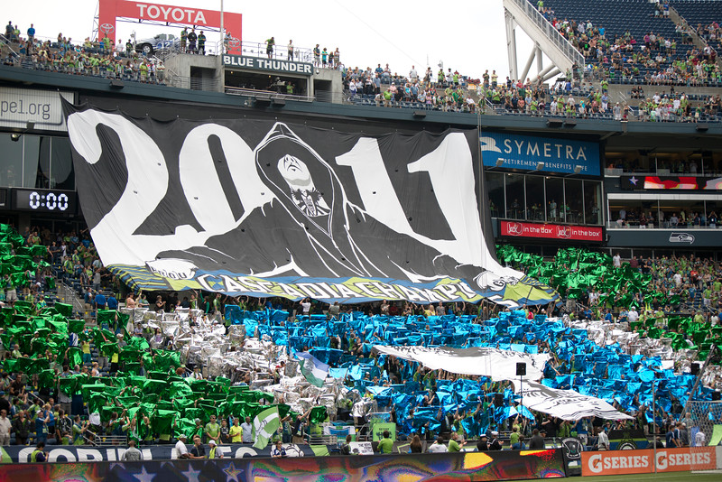 """The Tifo is finally spread out, showing a fan in a hoodie, the ECS logo tattooed on his throat, and """"BROU"""" """"GHAM"""" on his nuckles, over the Cascadia trophy on a field of blue, silver, and green."""