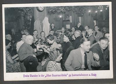 193608  Onderschrift: zie foto Niet in album 1936 of 1937. Reden: plaats in album. Geplaatst bij augustus 1936  Vier DHV-ers: vlnr: Jan Blom, Jan Peters, Piet Stegeman, Jo Alberts. Naast hem een mij onbekende man die ook op andere foto's van dit tochtje voorkomt. Hij doet de bestelling.  Deze vier en een mij onbekende maakten een reisje langs de Rijn. Ofschoon niet een reisje van de DHV geeft deze foto de sfeer vlak voor WO II in Duitsland goed weer. Een plaatselijke schone is ingepalmd. de man zittend derde van rechts vooraan (met licht pak) draagt een speldje met het hakenkruis. En een boksbeugel.   JanBlomcremealbum Fotograaf  onbekend Formaat 14 x 10.5 Afdruk zw