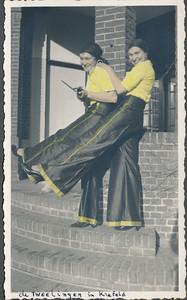 19360104 Onderschrift: de Tweelingen in Krefeld Opmerking: In Crefeld. De tweeling Jopie en Julie Broekhuis. Zie verslag in Clubnieuws februari 1936 van de tocht naar Crefeld op 4 en 5 januari 1936. Er staat: De drie in het hotel (d.i. Stadt Munchen) vertoevende dames wilden blijkbaar niet afsteken bij de talrijke heeren (echter als zoodanig ternauwnood kenbaar) en waren dus in travestie, men ziet er hier twee van. Foto in Clubnieuws zonder achtergrond. Zie ook Deventer Dagbld 6 januari 1936.  CollectieJanBlomcremealbum  Fotograaf: onbekend, mogelijk Jan Blom  Formaat; 11 x 6.5  Afdruk zw  ingekleurd