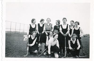 Achterop: Dev.I 1937-1938 Staand: Iet Resius, Sonja Delwig, Paula Bunschoten, Adri Huijzer, Trien Strabbing, Zus Hoetink, Mien Kip Voor: Gerda Breukelaar, Lot Brevet, Moi en Lien Tjeenk Willink Verder ook 90 % Foto is dus gereproduceerd, waar? Niet Clubnieuws ws. Hockeysport.  Ook achterop: Mejuffrouw A. Coldewey.  Opmerking: foto ook in Collectie Blom  enveloppe Drijver   Collectie Coldewey afkomstig Annet Coldewey  Fotograaf: prive afdruk Hakeboom Formaat: 9 x 6 Afdruk zw