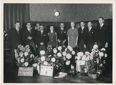 19381119 Achterop: Receptie bestuur DHV 25 jarig bestaan vlnr Heer J. Broekhuis, B. Meijer, J.Th.Peters, Juffr. Resius, Heer Drijver, Juff. Coldeweij, Heer P. Stegeman, J. Blom, H. vd Goot  Opmerking: dezelfde foto op iets ander moment in fotoalbum t.g.v. lustrum Daaruit het bovenste gedeelte in lustrumnummer Clubnieuws 1963, p. 30.  Receptie was in de Foyer van de Schouwburg om 4.30 n.m.  Op de grond vlnr: foto juniorestoernooi 16 november 1938 gemaakt door Van der Geijn, getekende en gekleurde plaat van U.D (?), blad met telegrammen, asbak aangeboden door de Dames-hockeybond, schilderstuk van Zutphen (ws. aangeboden door Zutphen, nog aanwezig clubhuis??)), het fotoalbum. Zie Clubnieuws december 1938 p. 42.    Collectie Arda Stegeman geschonken aan DHV augustus 2012 Fotograaf:Van der Geijn Formaat: 25 x 18  Afdruk zw